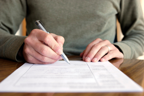 Man Filling Out Form on Table